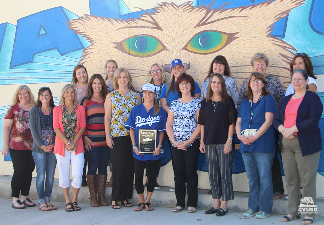 Teachers of Walnut Elementary standing in front of mural